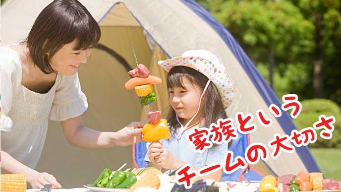 キャンプで子供とバーベキューの料理を作る母親