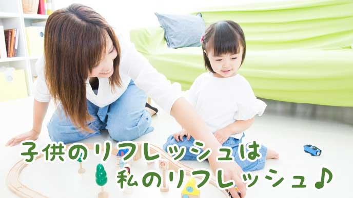 子供と一緒におもちゃで遊んでいる母親