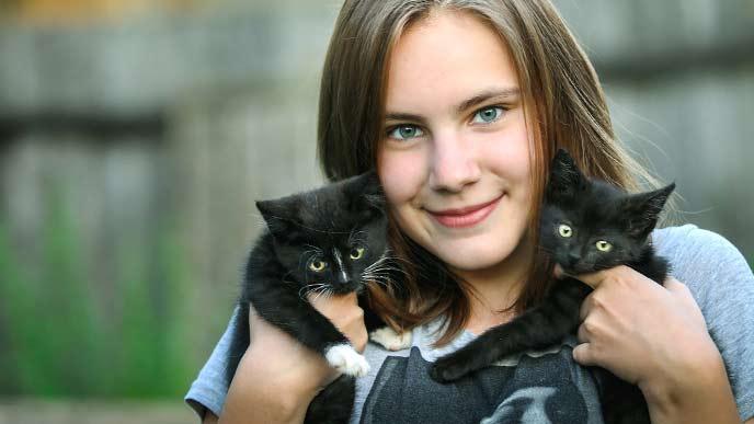 黒い猫二匹を両手で抱えている女性