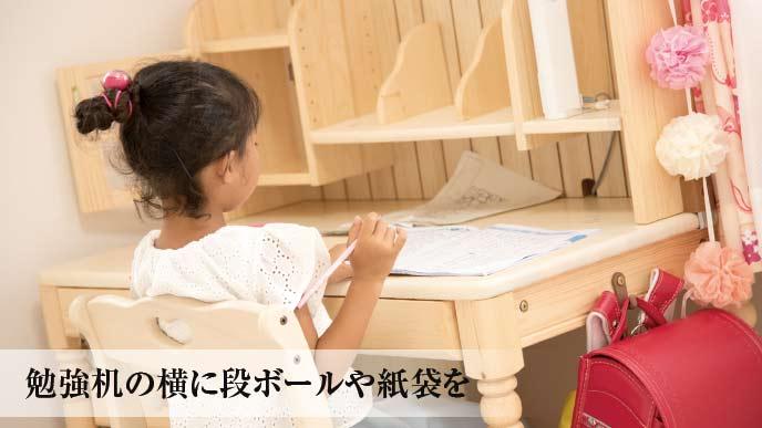 勉強机に座っている小学生の女の子
