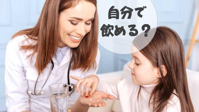 薬を子供に渡す母親と飲む準備をしている子供