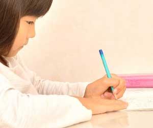 日記帳に字を書いている小学生の女の子