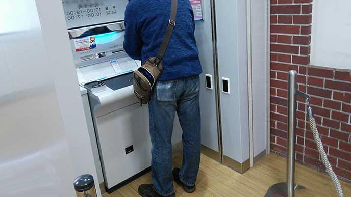 ATMで現金を引き出す男性