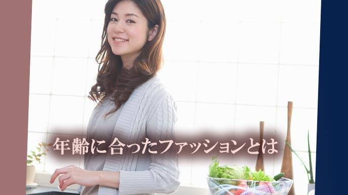 ミセスが無彩色のコーデで台所に立ち微笑んでいる
