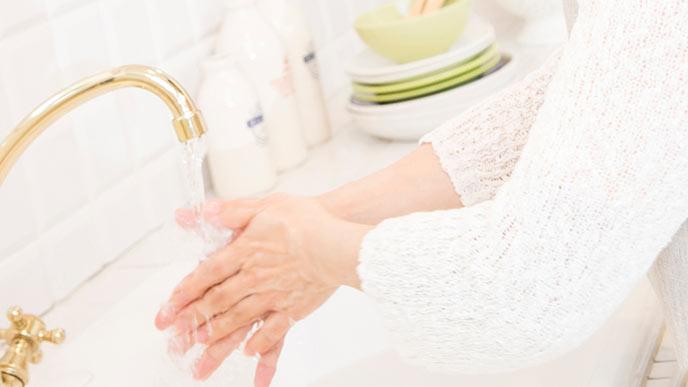 台所の流水で手洗いする女性