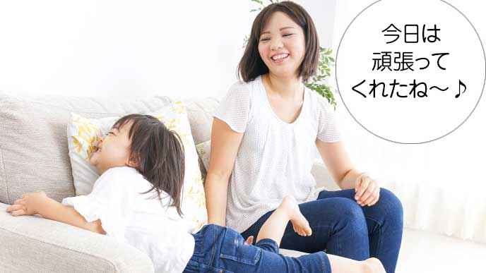 ソファーの上で子供を楽しんでいるお母さん