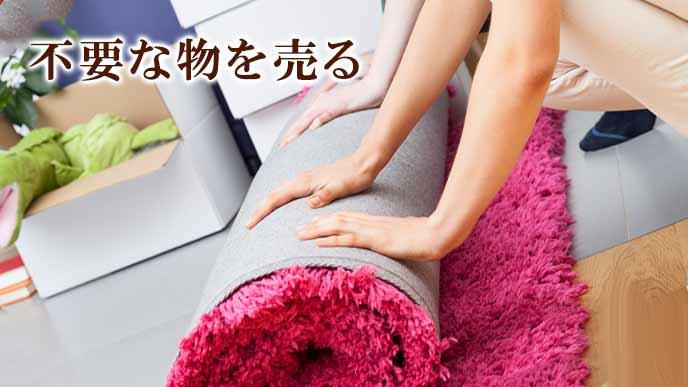 いらないカーペットを丸める女性