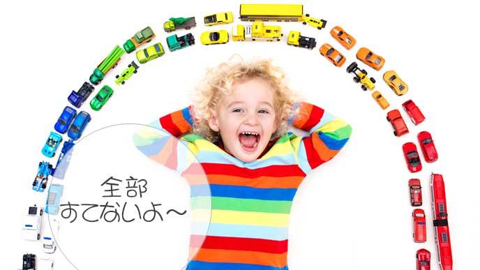 ミニカーを並べて自慢している外国の子供