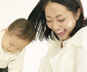 子供の傍で大きく口を開いて話す母親