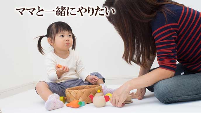 子供部屋と一緒に玩具の片づけをする母親