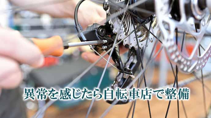 自転車店でブレーキの整備をする