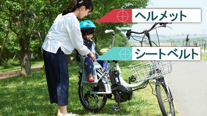 子供のシートベルトとヘルメットのチェックをする母親