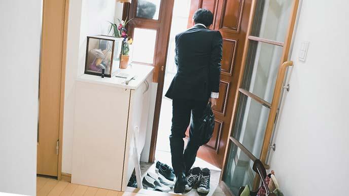 狭い玄関から出勤する男性