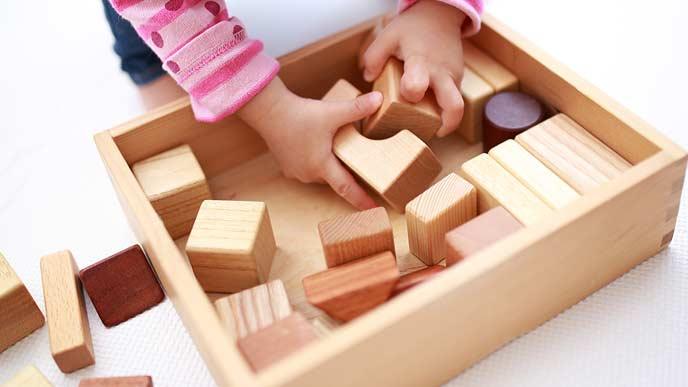 木製の積み木ブロックを箱から出す幼児