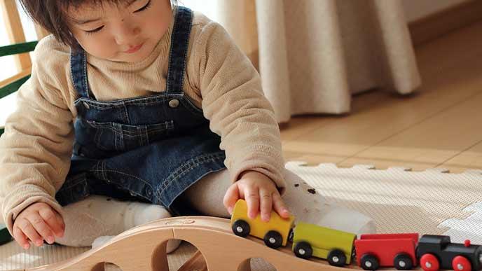 木製機関車を転がして遊ぶ幼児