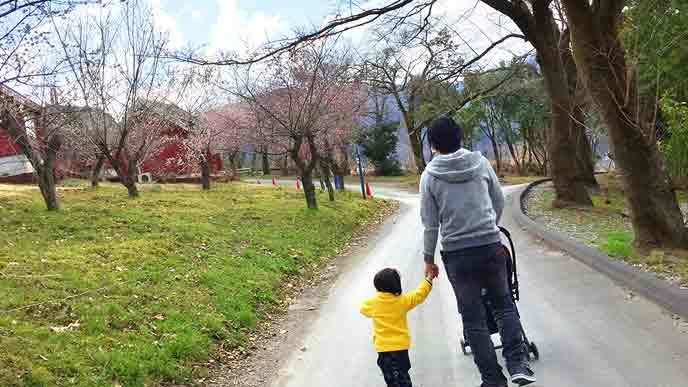 ベビーカーを押して歩く父親と手を引かれる幼児