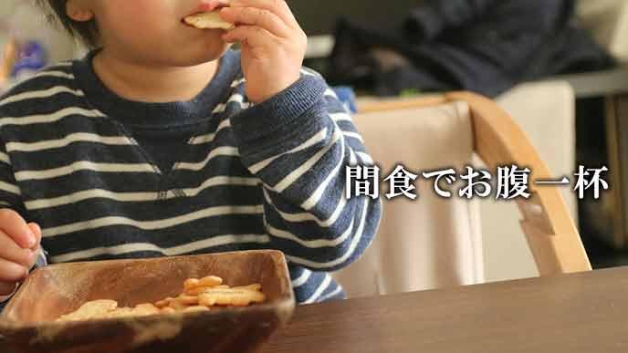 間食でスナック菓子を食べる子供