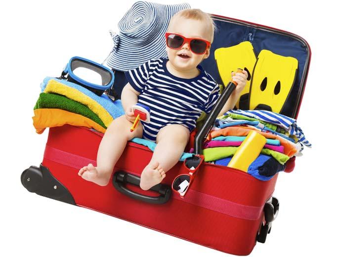 スーツケースの上で笑う幼児
