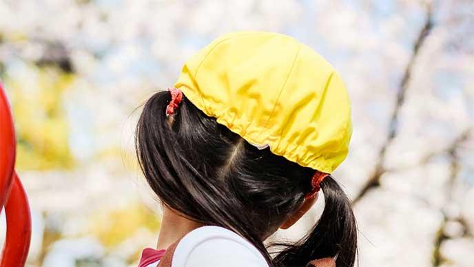 黄色い帽子をかぶってる幼稚園児