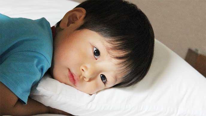 枕が気になって寝られない目を見開いてる男の子