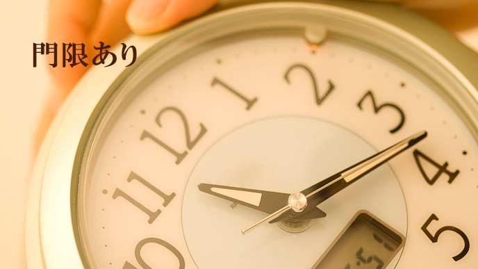 12時手前の時刻の時計を持つ女性の手