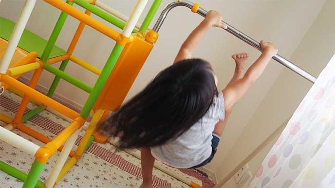 室内ジャングルジムについてる鉄棒にぶら下がってる女の子