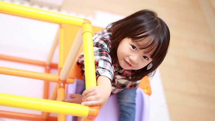 室内ジャングルジムについてる滑り台を滑ろうとsてる女の子