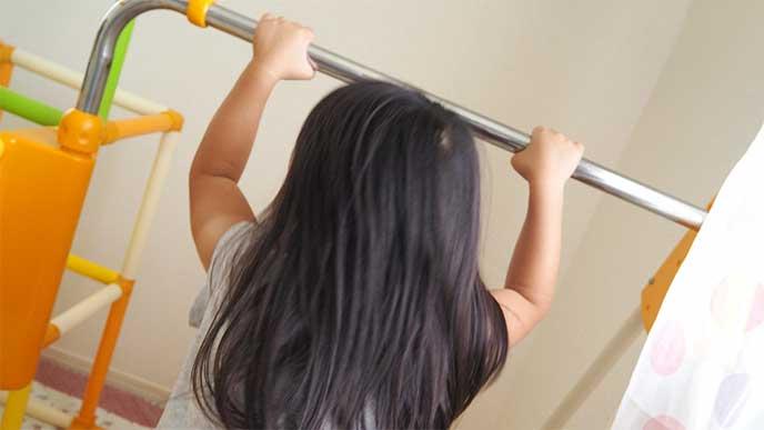 室内用ジャングルジムの鉄棒で遊んでる女の子