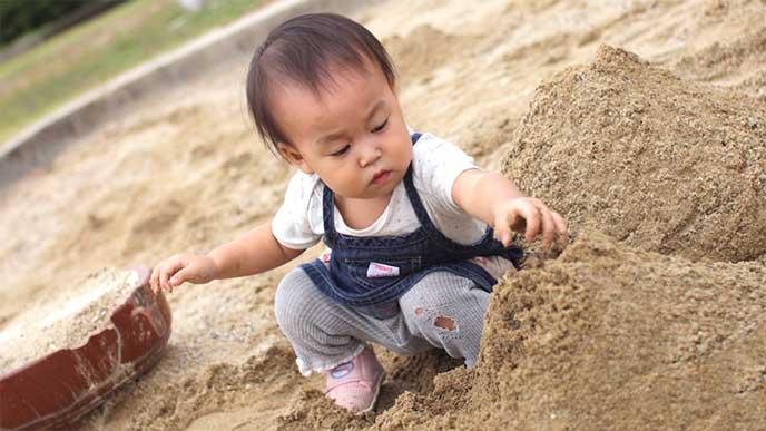 砂場で遊んでる赤ちゃんn