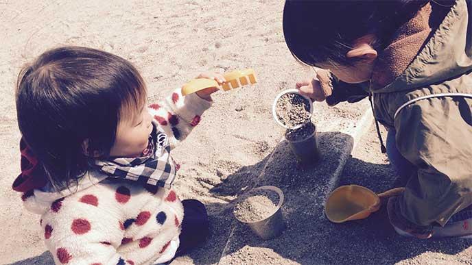 友達と一緒に砂遊びをしてる女の子