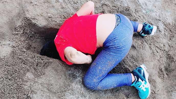 服を砂まみれにして砂場で遊んでる男の子