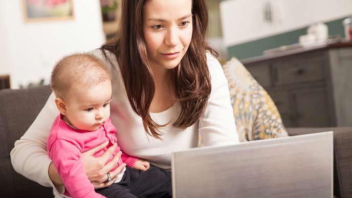 パソコンで職探しする母親