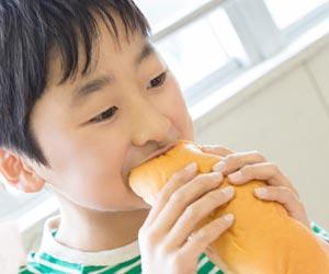 給食のパンにかじりつく子供