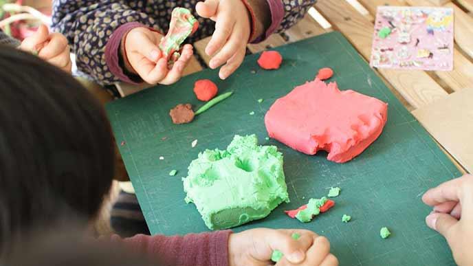 粘土で共同作業する子供達