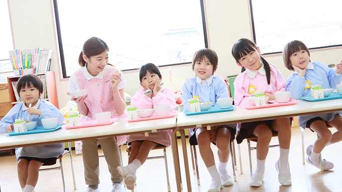 幼稚園で園児が並んでお昼の食事をとっている
