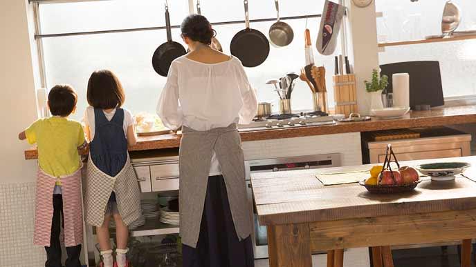 台所に立つ母親と子供達