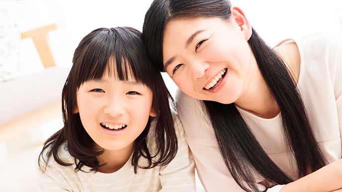 頭を並べて微笑む母親と娘