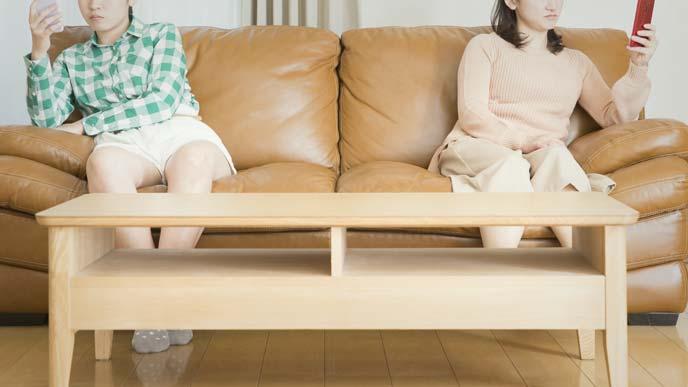 同じソファの両端に座りそれぞれスマホをいじっている女子高生と母親