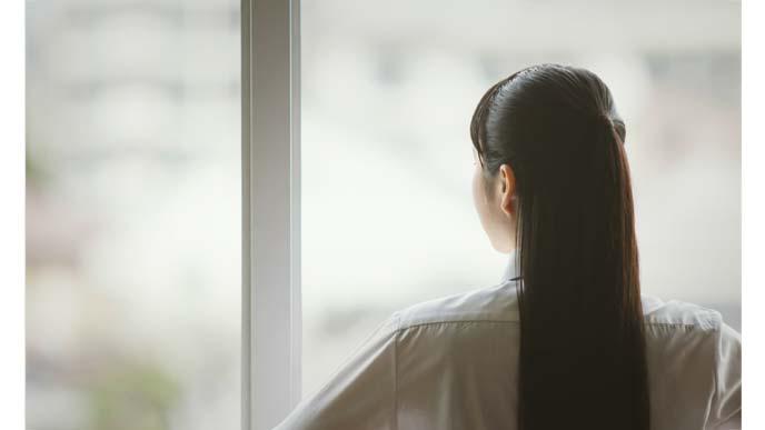 教室の窓からぼんやりと外を眺める女子高校生