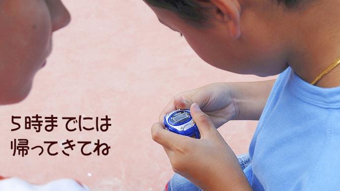 腕時計を持つ子供と約束させる親