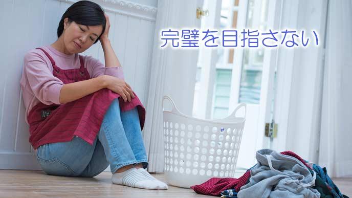 洗濯物の前でしゃがみ込む主婦