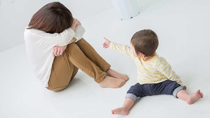 子供の傍で育児に疲れてふさぎ込む 母親