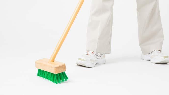 デッキブラシでベランダの床を洗う