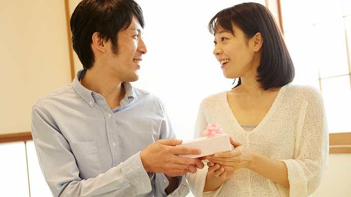 小さな箱のプレゼントを持って笑顔の夫婦