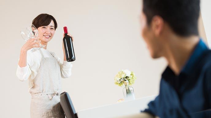 ワイングラスとワインボトルを持って夫に笑いかける妻