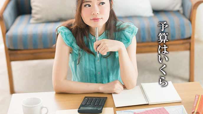 家計簿をつけながら考える女性