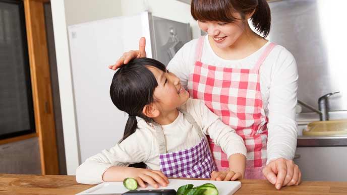 料理のお手伝いをする子供を褒める母親