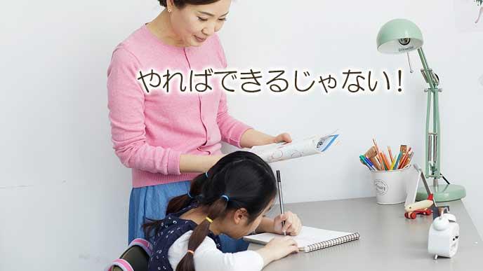 勉強する子供を褒める母親