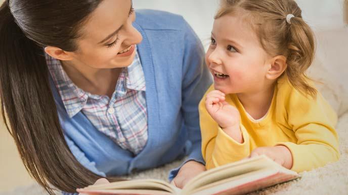 小さな女の子に読み聞かせする若い母親