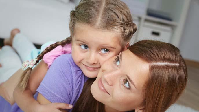 母親の背に乗り頬ずりして甘える幼女
